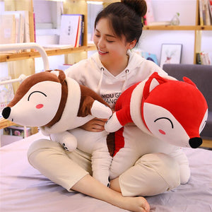 girl hugging brown fox plushie and red fox plushie