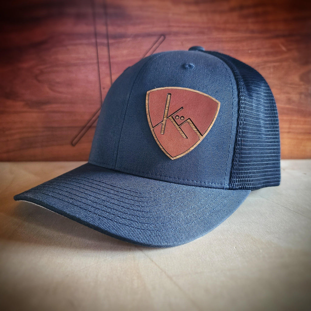 Navy blue snapback trucker with smooth brown leather and wood badge