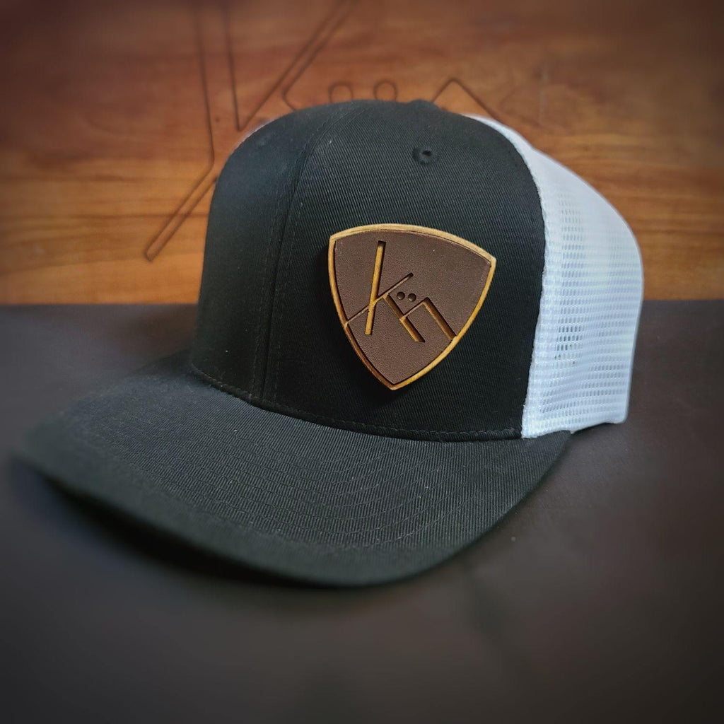 black and white snapbrack trucker with smooth brown leather and wood badge