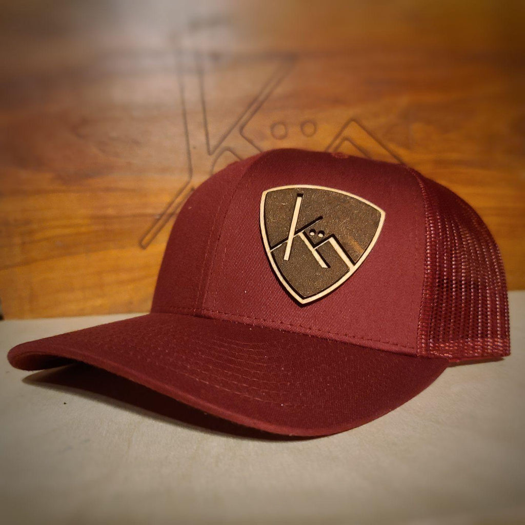 Cranberry snapback trucker with smooth brown leather and wood badge