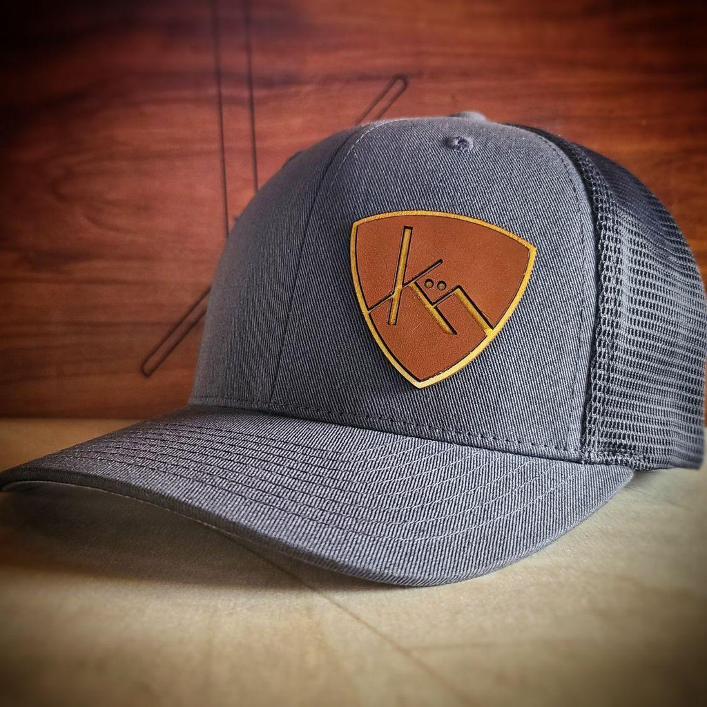 charcoal and gray snapback trucker with smooth brown leather and wood badge