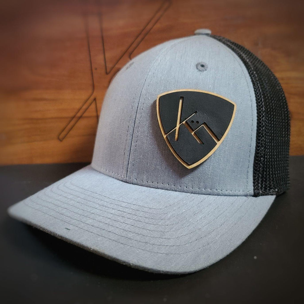 heather grey and black snapback trucker with smooth black leather and wood badge