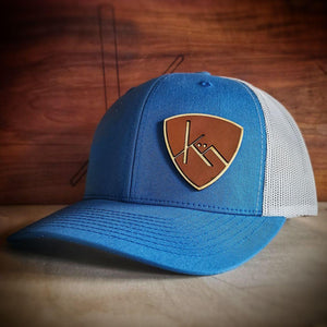Steel blue and white snapback trucker with smooth brown leather and wood badge