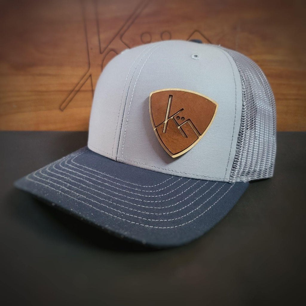 Navy gray snapback trucker with smooth brown leather and wood badge