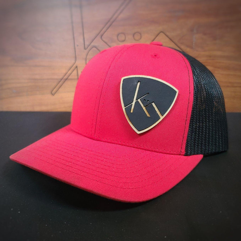Red and black snapback trucker with smooth black leather and wood badge