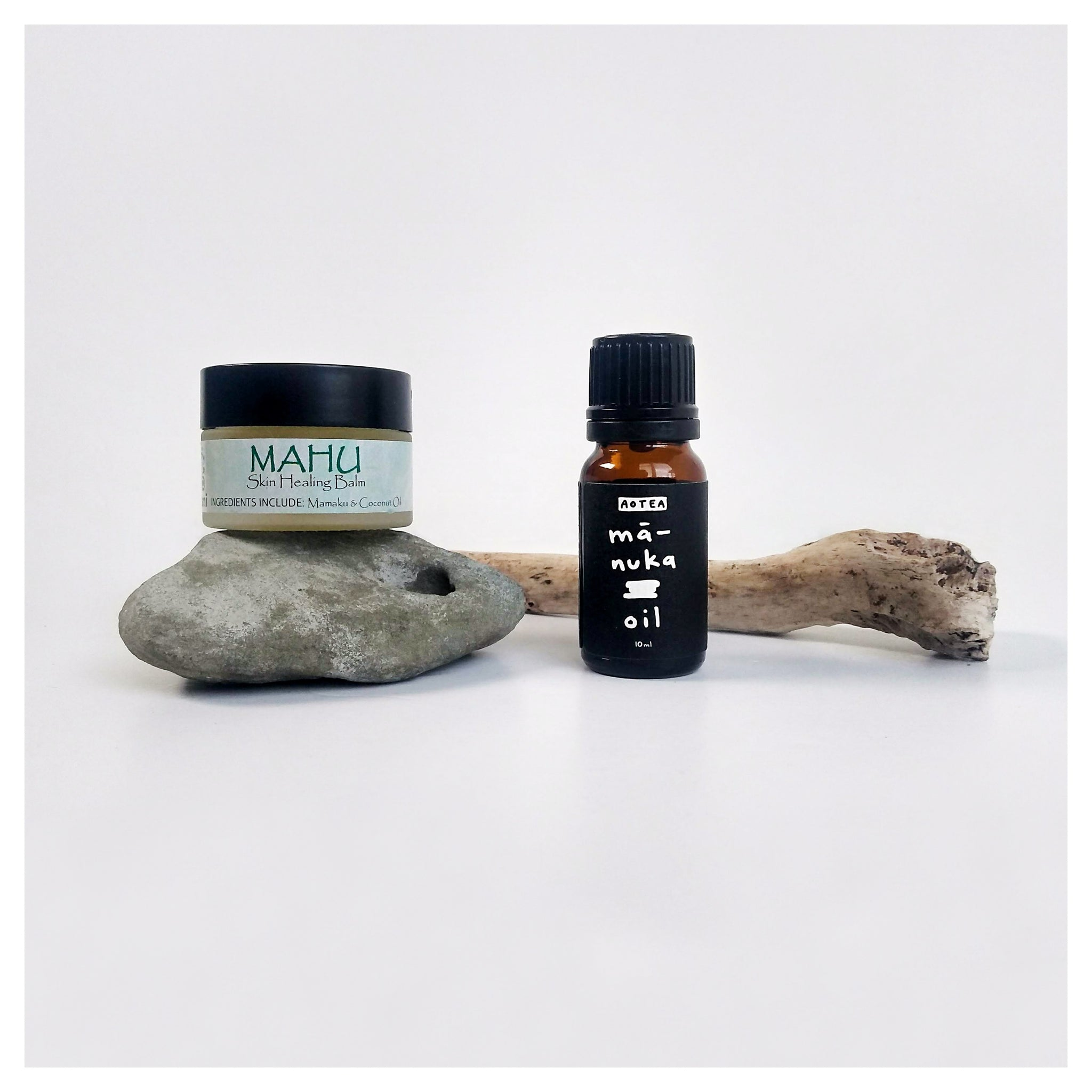 Hauora products (natural skincare) displayed with a stone and stick. The products are a rongoā Māori (rongoā rākau) balm and pure mānuka oil.