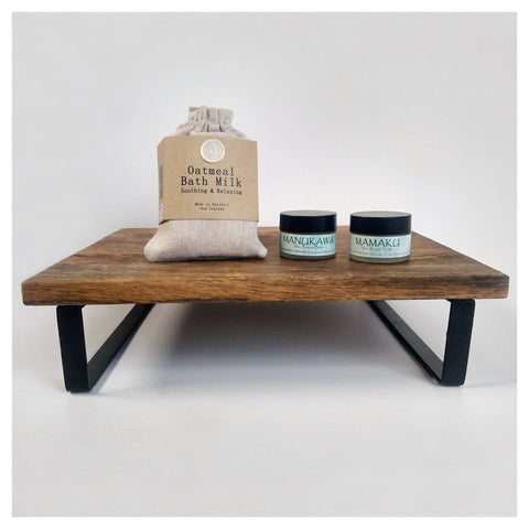 A natural skincare kit featuring rongoā Māori (rongoā rākau) balms and an oatmeal bath milk. In this image, the products are displayed on a wooden stand.
