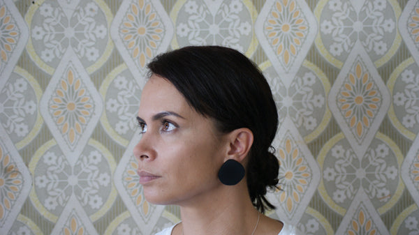 Woman wearing large black handmade polymer clay earrings