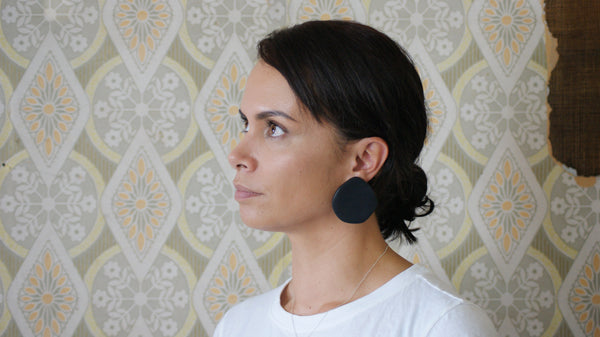 Woman wearing extra large black polymer clay organic shaped studs