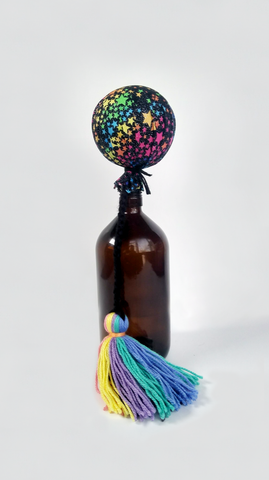 Contemporary Māori poi by Koakoa Design in a cotton galaxy fabric with a sorbet rainbow tail. The poi is displayed on top of a brown bottle.