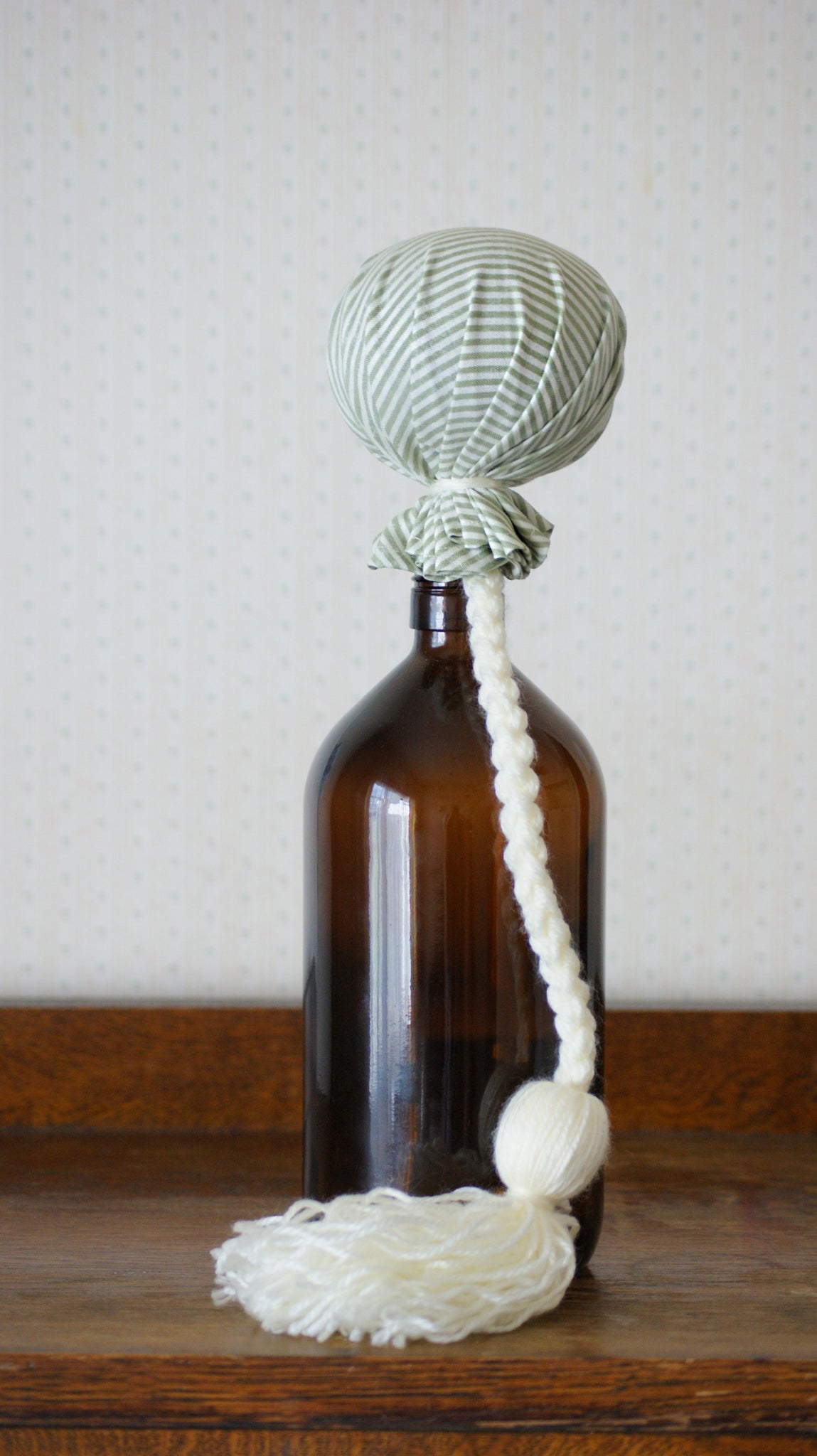 Handcrafted poi made in NZ. The poi is covered in a vintage style green and cream striped cotton fabric.