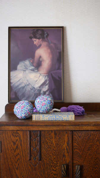 Two Māori poi covered in a vintage-style floral fabric not plastic. The poi are lying in front of a vintage print of a woman in a petticoat. Also lying on the oak dresser is a vintage fairy tale book.