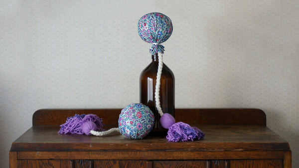 Pair of handcrafted NZ poi. The poi balls are covered in a floral fabric with blue-green tones and a vintage aesthetic.