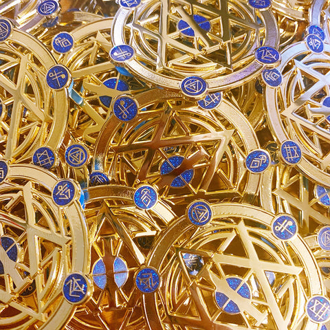 A bunch of gold die cut pins