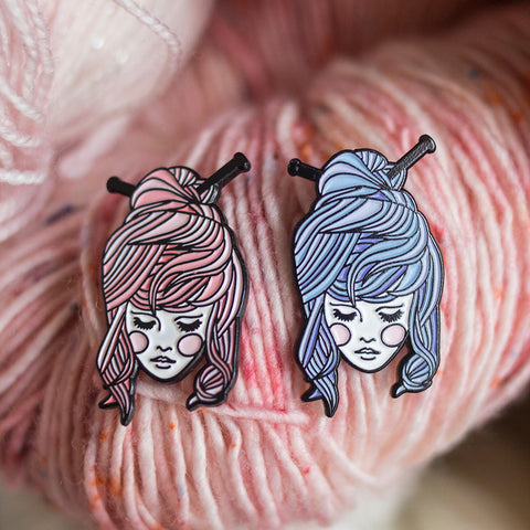 enamel pins of a girl with knitting needles in her hair, in pink and blue