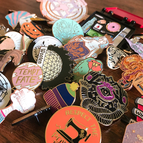 an assortment of enamel pins by Alchemy Merch
