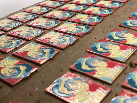 a tray of enamel pins curing after being inked