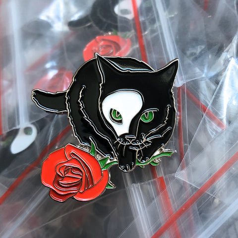 A soft enamel pin of a black cat wearing a half-mask and holding a rose, by Braden Duncan