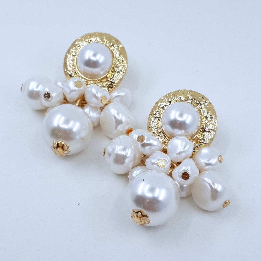 Liv is totally gorgeous loaded pearl earring! These earrings are an elegant gold dangle earring adorned with a cluster of pearl beads. They are the perfect earring for a wedding or evening outfit.