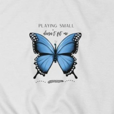 A women's white crew-neck sweatshirt  with a butterfly design and quote Playing small doesn't fit me