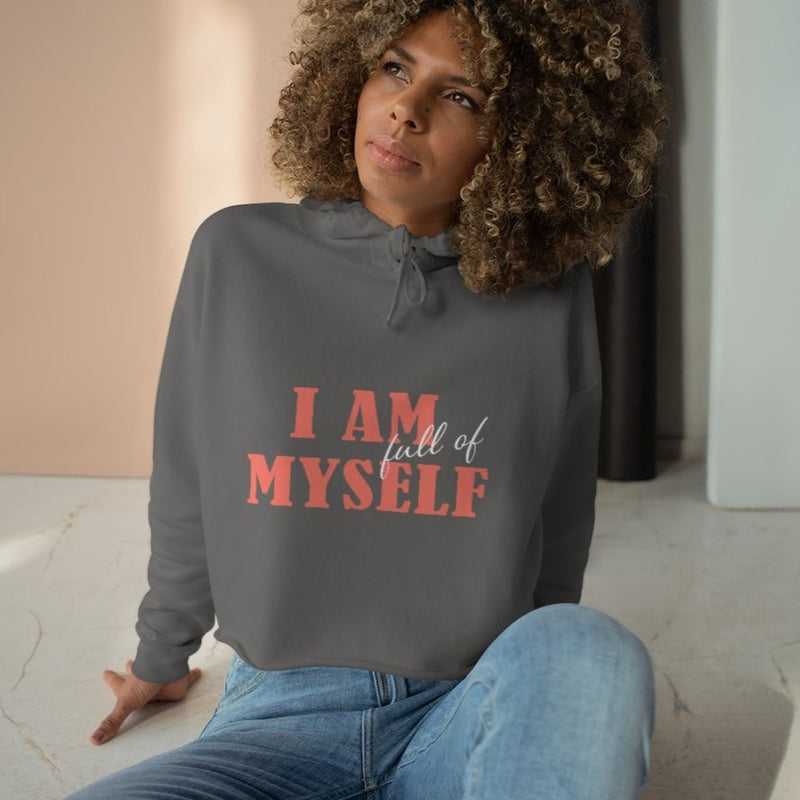 A woman sitting on a floor wearing a grey crop hoodie with a quote I am full of myself