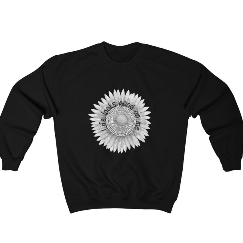 A black  crewneck sweatshirt with a sunflower deign and quote Life looks good on me