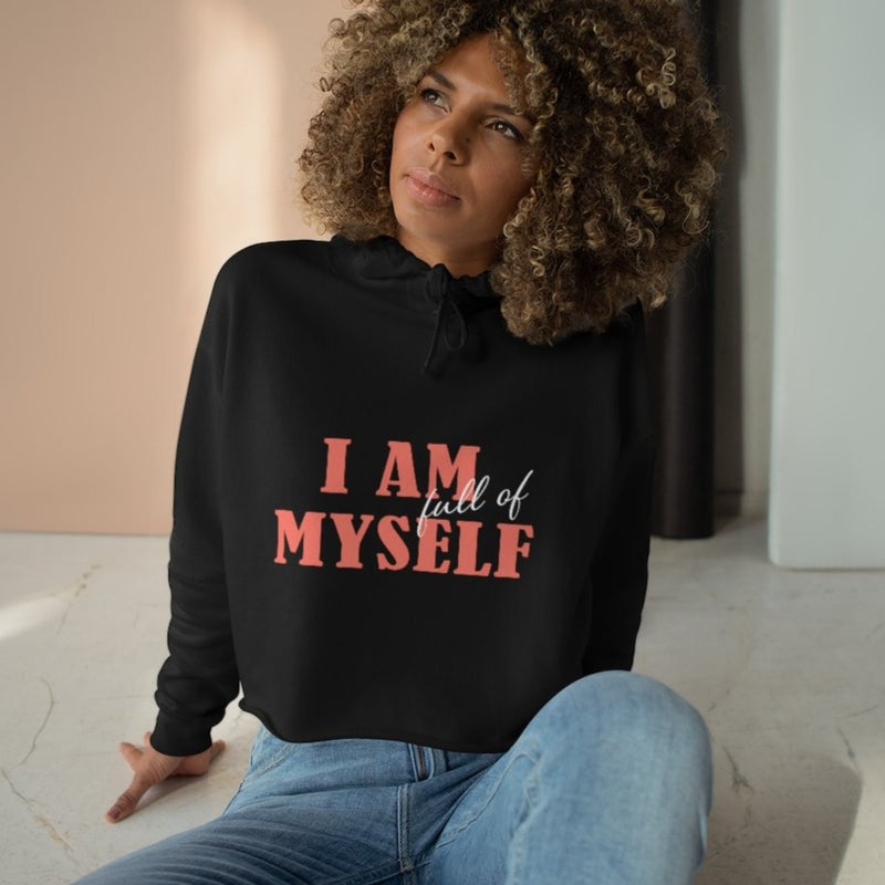 A woman sitting on a floor wearing a black crop hoodie with a quote I am full of myself