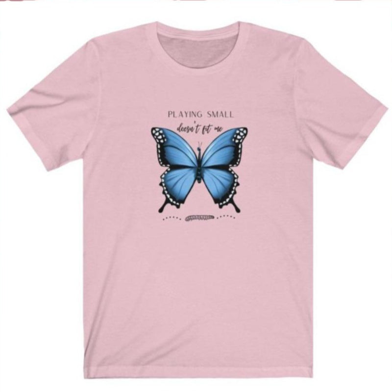 A pink crewneck t-shirt with a butterfly design and quote playing small doesn't fit me