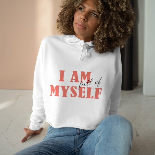 A woman sitting on a floor wearing a white crop hoodie with a quote I am full of myself