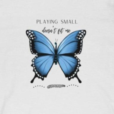 A white crewneck t-shirt with a butterfly design and quote playing small doesn't fit me