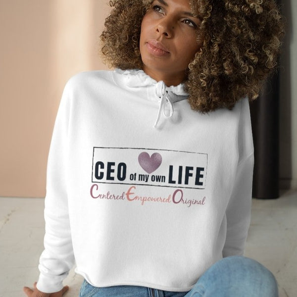 A woman sitting on a floor wearing a white crop hoodie with a quote CEO Centered Empowered Original