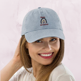 A woman in a studio wearing denim baseball hat with a rainbow design and quote Divine Sisterhood