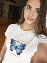A woman wearing a white t-shirt with a butterfly design and quote Playing small doesn't fit me