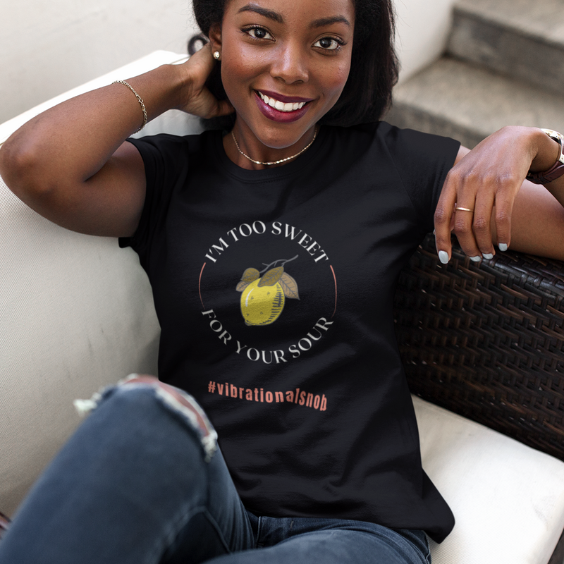 A young smiling girl sitting on a sofa and wearing a black crewneck tee with a quote I'm too sweet for your sour, #vibrational snob and picture of lemon.