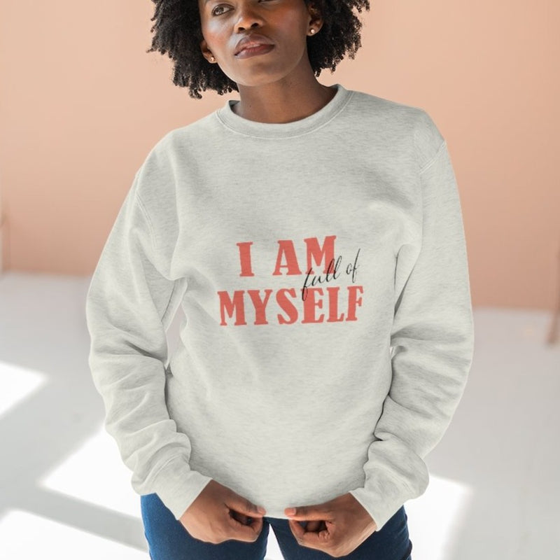 A woman wearing an oatmeal color crew-neck sweatshirt with a quote I am full of myself