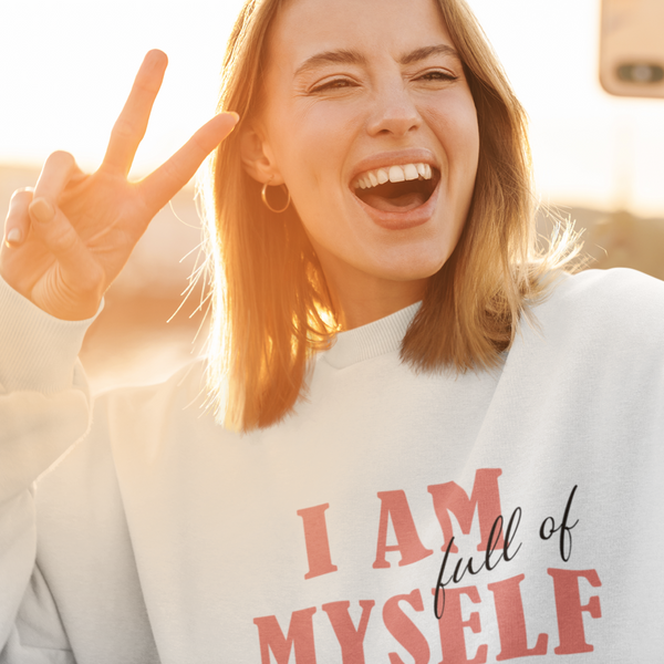 A happy woman taking a selfie and wearing a white crewneck sweatshirt with a quote I am full of myself