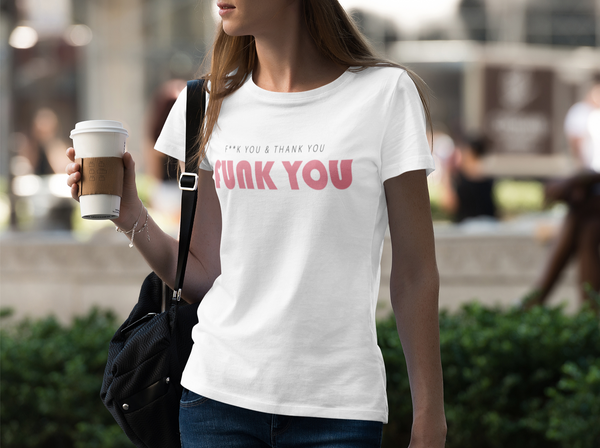 A woman holding a coffee on the street and wearing a white crew-neck t-shirt with a quote Funk you