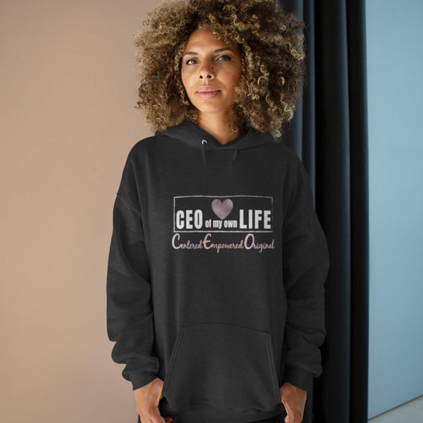 A woman standing in a hallway wearing a grey hoodie with a quote CEO Centered Empower Original