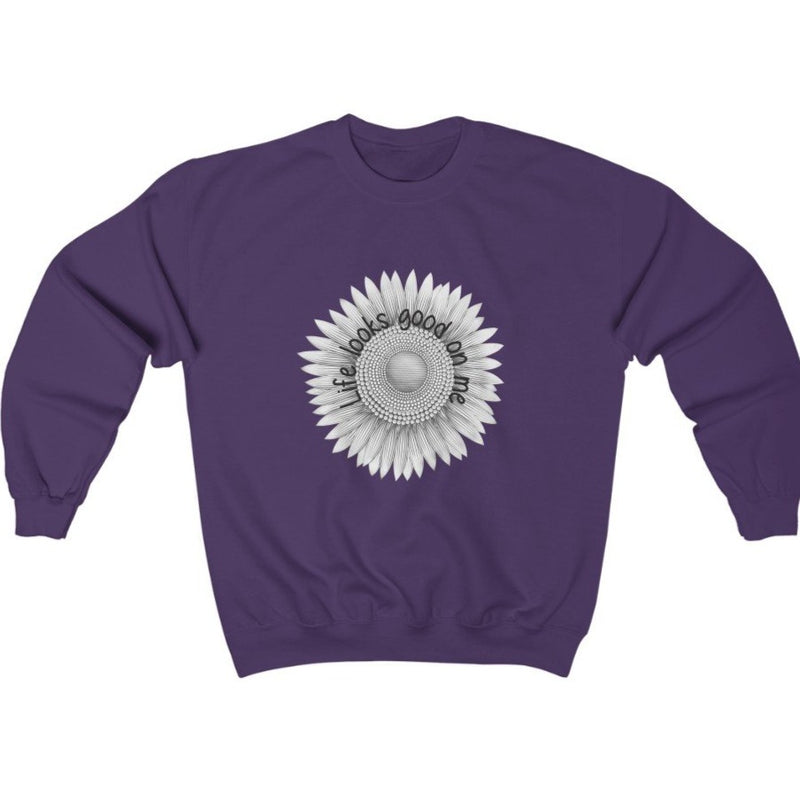 A purple crewneck sweatshirt with a sunflower deign and quote Life looks good on me
