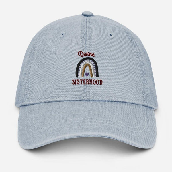 A denim baseball hat with a rainbow design and quote Divine Sisterhood
