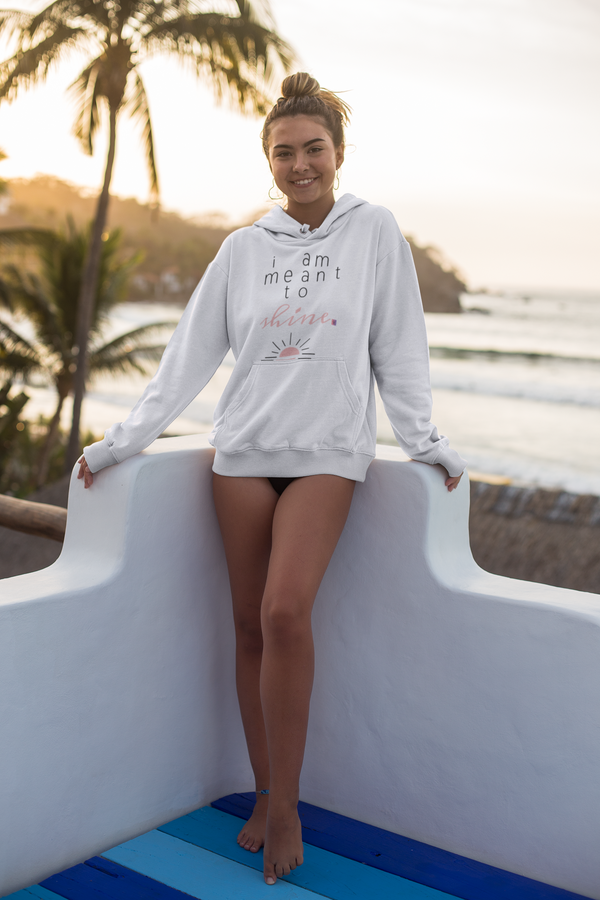 A smiling woman at sunset wearing a hoodie in white with a design I am meant to shine