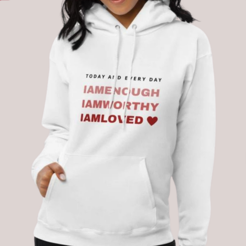 A young woman at a studio wearing hoodie in grey with a quote I am Enough, I am worthy, I am loved