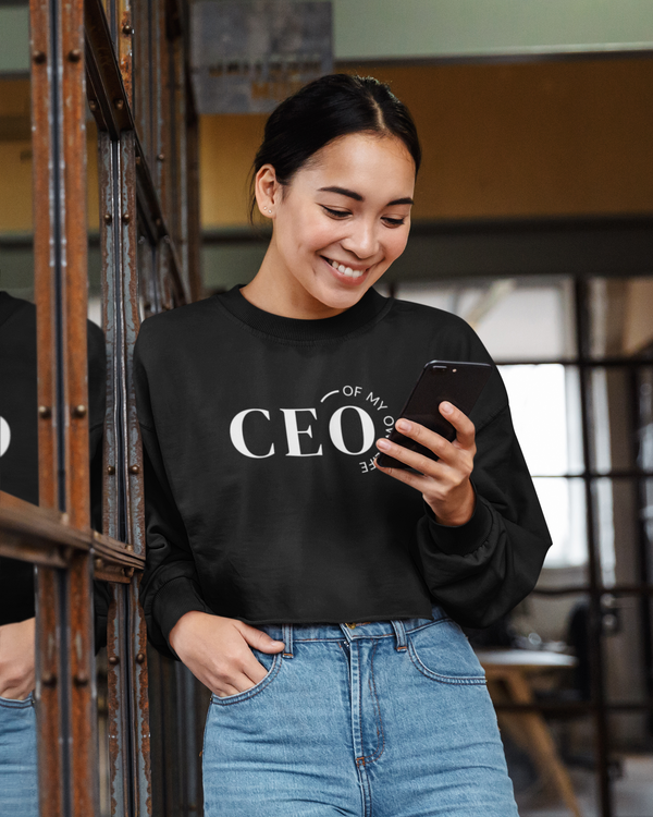 A happy woman at an office wearing a crop top sweatshirt in black with a quote CEO of my own life