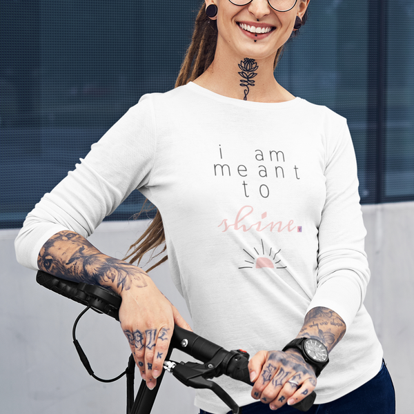 A happy woman with tattoos wearing a white crew-neck long sleeve with a quote I am meant to shine