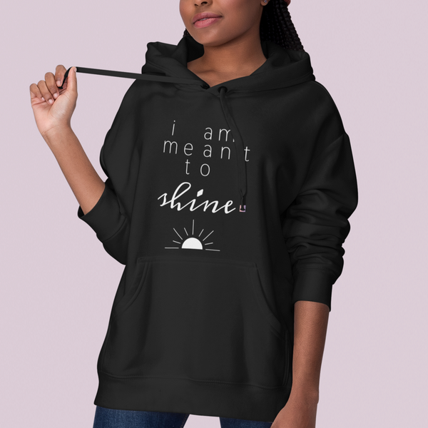 A woman at a studio wearing a black hoodie with a quote I am meant to shine