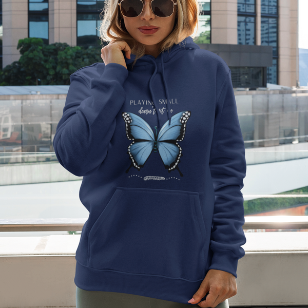 A woman posing by a tall building and wearing  navy hoodie with a butterfly design and quote Playing small doesn't fit me