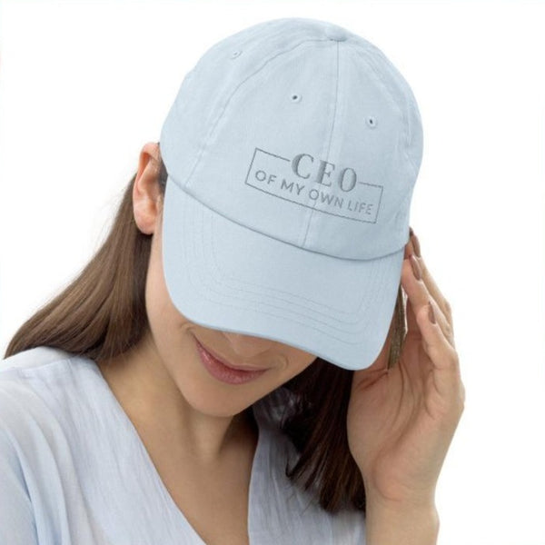 A woman in a studio wearing a pastel blue baseball hat with a quote CEO of my own life