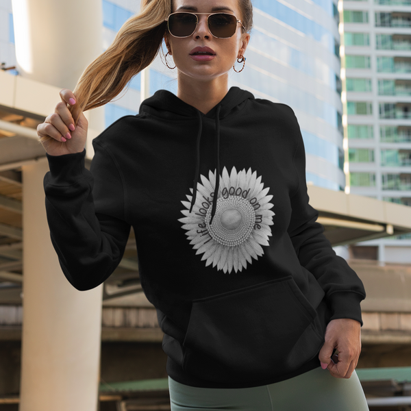 A woman in front a tall building posing and wearing a hoodie in black with a sunflower design and quote Life looks good on me