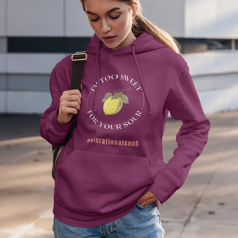 A young woman in front of a building wearing jeans and maroon hooded sweatshirt with a design I'm too sweet for your sour, #vibrationalsnob and lemon.