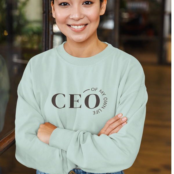 A woman with crossed arms wearing a crop top sweatshirt in mint with a quote CEO of my own life